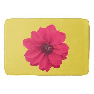 rosa Blume auf gelber Badematte