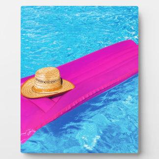 Rosa Luft mattrass mit Hut im Swimmingpool Fotoplatte