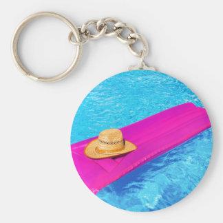 Rosa Luft mattrass mit Hut im Swimmingpool Schlüsselanhänger