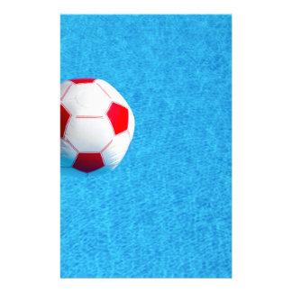 Rot-weißer Wasserball, der in Swimmingpool Briefpapier