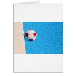 Rot-weißer Wasserball, der in Swimmingpool Karte