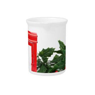 Rote Laterne mit den tealight Stechpalmenzweigen Getränke Pitcher