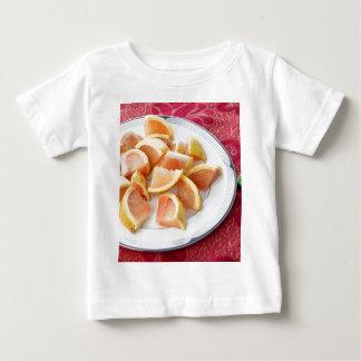 Rote Pampelmusen-Stücke auf einer runden Platte Baby T-shirt