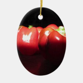 Rote Paprikaschoten belichtet durch Sonnenschein Ovales Keramik Ornament