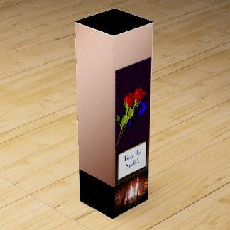 Rote und blaue Rose auf dem kupfernen Kamin mit Wein-Geschenkverpackung