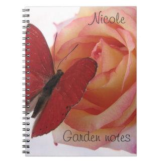 roter Schmetterling auf rosa Rosennotizbuch Spiral Notizblock