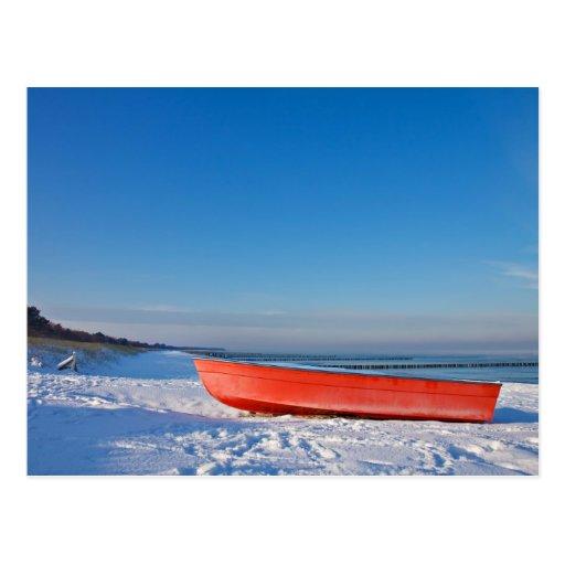 Rotes Boot auf Ufer der Ostsee im Winter Postkarten
