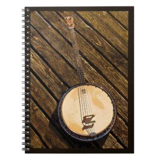 Rustikales Banjo-Musik-Instrument auf hölzernem Notizblock
