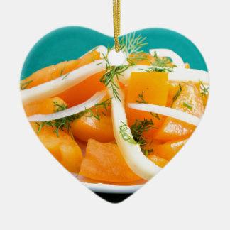 Scheiben der orange Tomate auf einer Platte mit Keramik Ornament