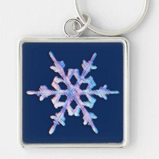 Schillernde Schneeflocke auf dunkelblauem Schlüsselanhänger