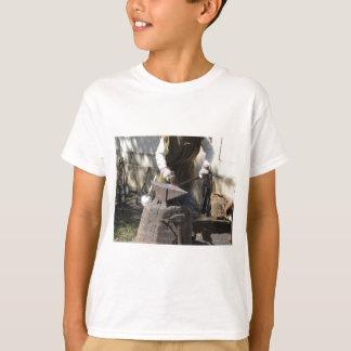 Schmied, der manuell das flüssige Metall schmiedet T-Shirt