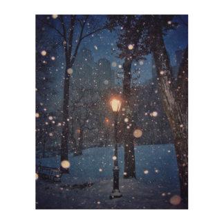 Schnee, der um eine Straßenbeleuchtung wirbelt Holzdruck