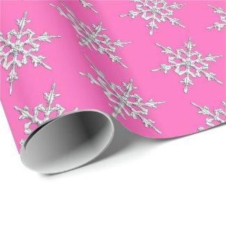 Schneeflocken, silberne Kristalle auf pinkfarbenem Geschenkpapier