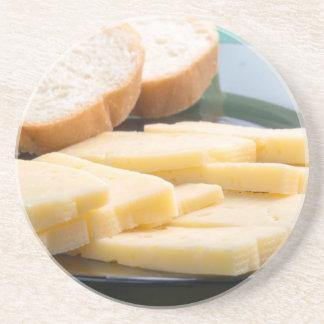 Schneiden Sie Scheiben des Käses auf einer Sandstein Untersetzer