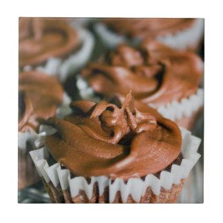 Schokoladen-mattierte kleine Kuchen auf einem Kleine Quadratische Fliese