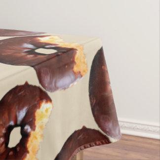 Schokoladen-mattierter gelber Kuchen-Krapfen mit Tischdecke