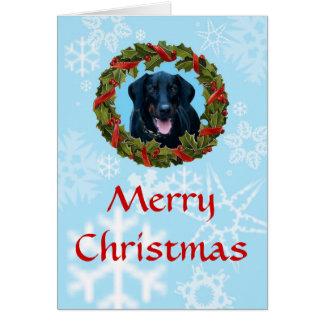 Schwarze Dobermann-Weihnachtskarte mit Kranz und Karte