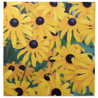 Schwarze mit Augen Susan-Blumen in dunkelgelbem Serviette