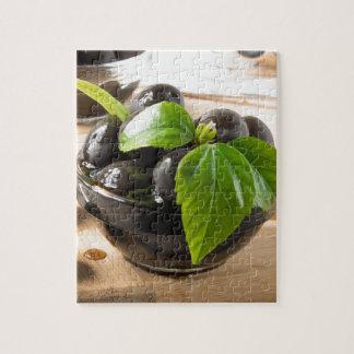 Schwarze Oliven auf einer Tabelle und Glasschalen Puzzle