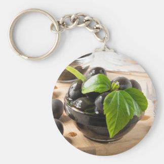 Schwarze Oliven auf einer Tabelle und Glasschalen Schlüsselanhänger