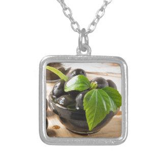 Schwarze Oliven auf einer Tabelle und Glasschalen Versilberte Kette
