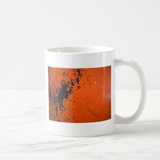 Schwarzer Farben-Spritzer auf Orange Kaffeetasse