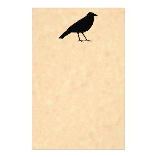 Schwarzer Krähen-Vogel auf einem Pergament-Muster Druckpapier