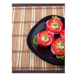 Schwarzer Teller mit geschnittenen Tomaten und Postkarte