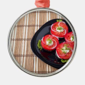 Schwarzer Teller mit geschnittenen Tomaten und Rundes Silberfarbenes Ornament