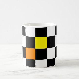 Schwarzes, weißes Schachbrett mit gelb-orangeer Kaffeetasse