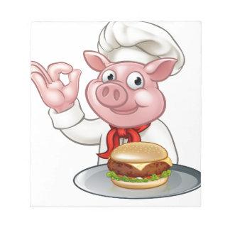 Schwein-Koch, der Burger hält Notizblock