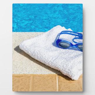 Schwimmenschutzbrillen und -tuch nahe Swimmingpool Fotoplatte