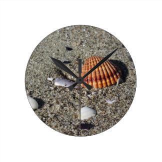 Seashells auf Sand Sommer setzen Draufsicht des Runde Wanduhr