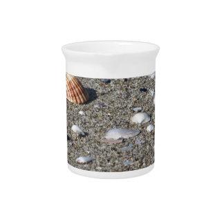 Seashells auf Sand. Sommerstrandhintergrund Krug