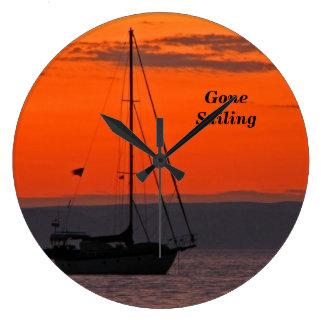 Segelboot an der Sonnenuntergang-Uhr, orange Große Wanduhr