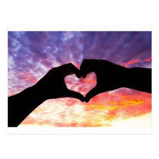 Silhouettehand in der Herzform und im schönen Postkarte