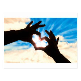 Silhouettehände in der Herzform und im blauen Postkarte