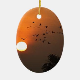 Sonnenaufgang mit Mengen der Fliegenkräne Ovales Keramik Ornament