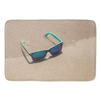 Sonnenbrille auf dem Strand Badematte