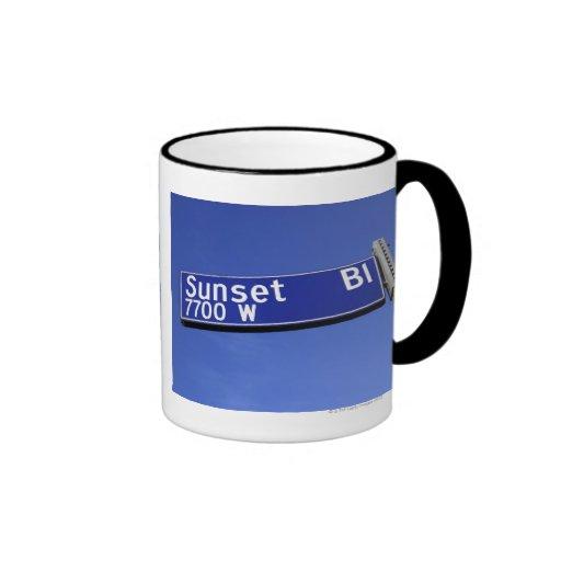 Sonnenuntergang-Boulevardzeichen gegen einen blaue Kaffeetasse