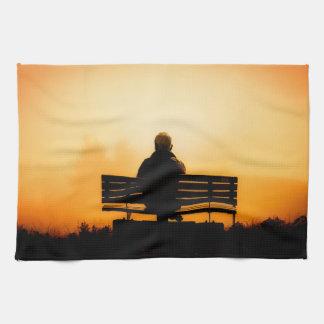 Sonnenuntergang-Szene mit Mann auf Bank Handtuch