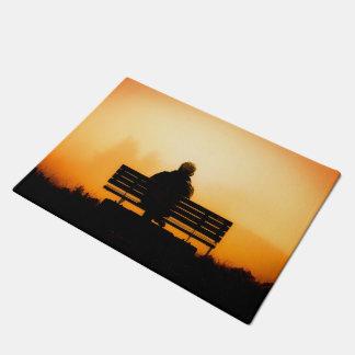 Sonnenuntergang-Szene mit Mann auf Bank Türmatte