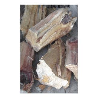 Stapel des unregelmäßig gehackten Brennholzes auf Briefpapier