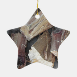 Stapel des unregelmäßig gehackten Brennholzes auf Keramik Stern-Ornament