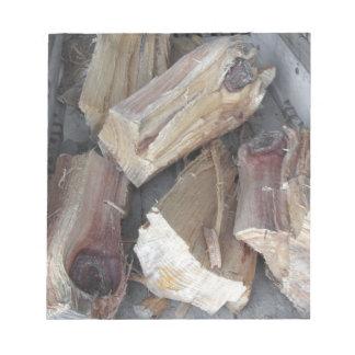 Stapel des unregelmäßig gehackten Brennholzes auf Notizblock