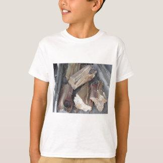 Stapel des unregelmäßig gehackten Brennholzes auf T-Shirt