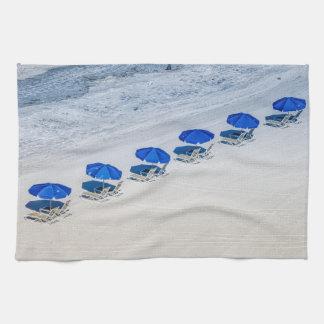 Strand-Stühle mit blauem Regenschirm auf Geschirrtuch