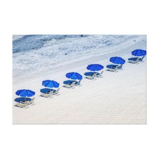 Strand-Stühle mit blauen Regenschirmen auf Leinwanddruck
