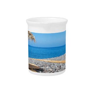Strandschirme mit Weg und Steine an der Küste Getränke Pitcher
