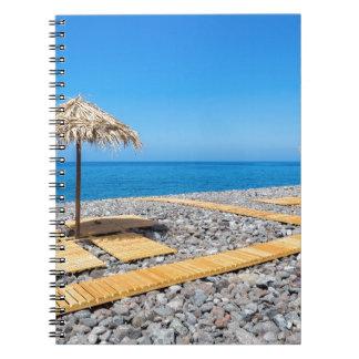 Strandschirme mit Weg und Steine an der Küste Spiral Notizblock